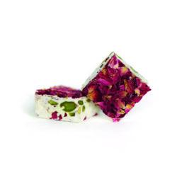Deux nougats avec des pistaches et des pétales de rose.