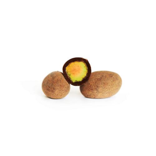 Trois pistaches enrobées de chocolat au lait, une d'elles est découpée avec la pistache visible.