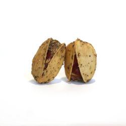 Deux pistaches en coque avec des herbes dessus.